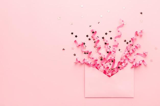 Esplosione di coriandoli. busta, stelle filanti festive, glitter sul rosa