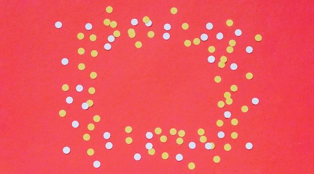 Cornice di coriandoli su sfondo rosso di carta rossa, posto per testo, logo, design