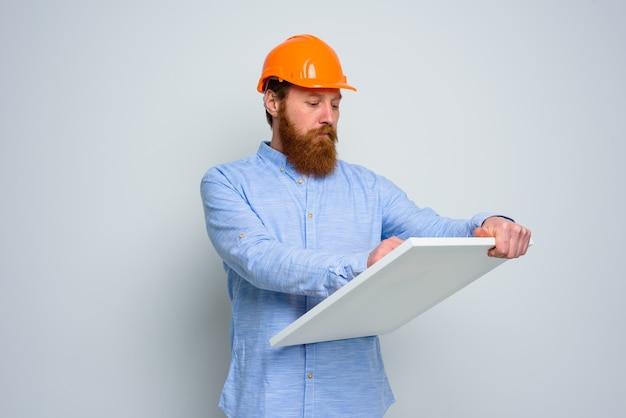 Architetto confidente con barba e casco arancione fa uno schizzo