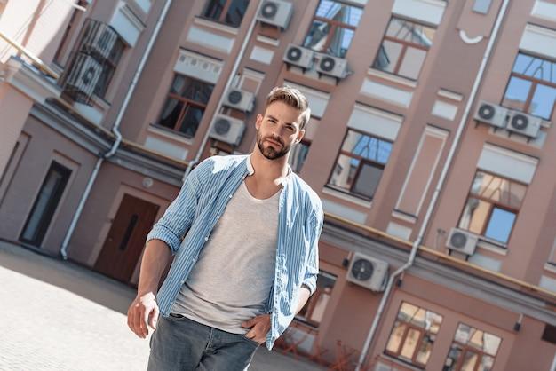 Fiducia serio uomo dai capelli castani con gli occhi azzurri che cammina fuori la mattina e guarda