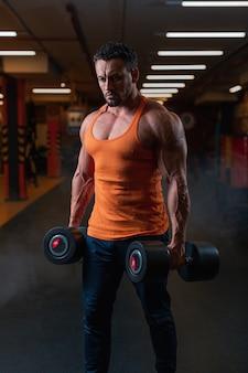 Fiducioso atleta maschio adulto in maglia arancione si trova in palestra con manubri.