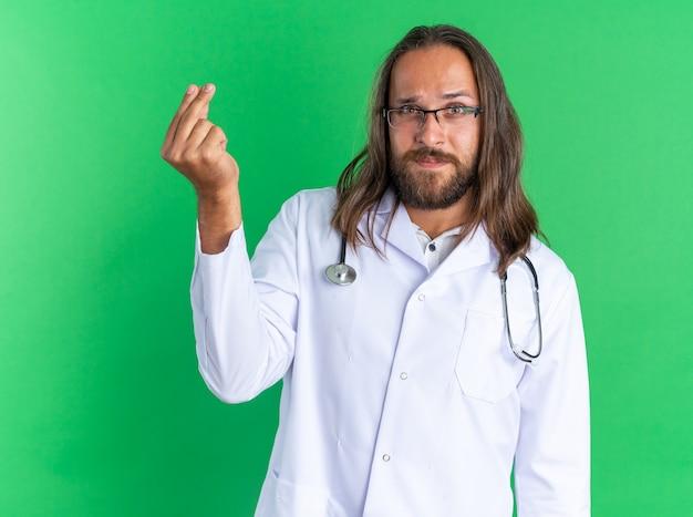 Fiducioso medico maschio adulto che indossa tunica medica e stetoscopio con occhiali che fanno gesti di denaro