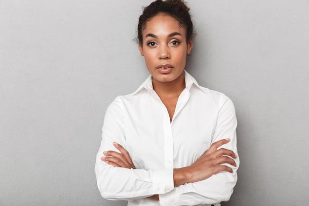 Fiducioso africano donna d'affari che indossa una camicia in piedi isolato