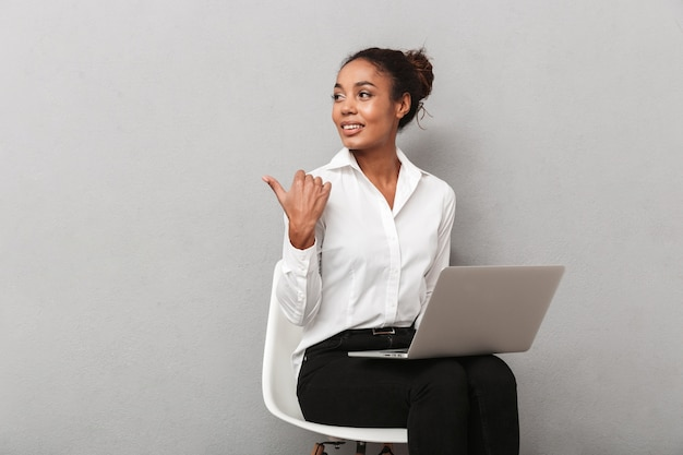 Fiducioso africano donna d'affari che indossa tuta seduto su una sedia, utilizzando il computer portatile su grigio