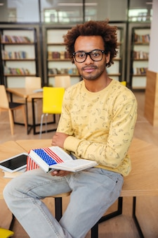 Fiducioso giovane africano con gli occhiali che legge un libro in biblioteca
