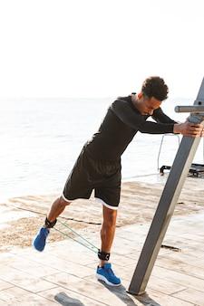 Fiducioso sportivo afroamericano che si esercita con l'espansore all'aperto in spiaggia