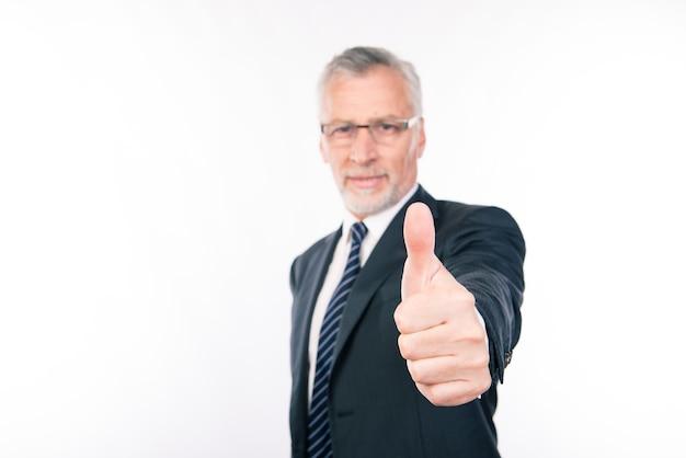 Uomo d'affari invecchiato sicuro che mostra pollice in su