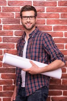 Architetto sicuro. bel giovane con gli occhiali che tiene il progetto e sorride mentre sta in piedi contro un muro di mattoni