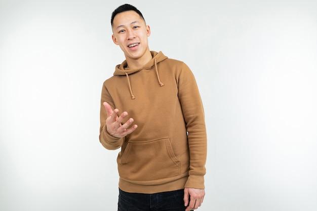 Uomo asiatico sicuro in maglia con cappuccio marrone su bianco