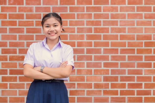 Sorriso felice uniforme incrociato del braccio dello studente della donna asiatica sicura con lo spazio della copia del muro di mattoni.