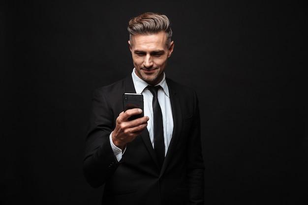 Fiducioso uomo d'affari attraente che indossa un abito in piedi isolato su un muro nero, usando il telefono cellulare, celebrando il successo