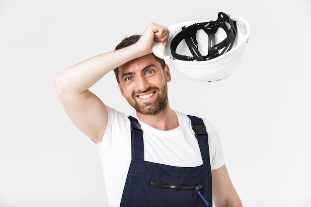 Fiducioso costruttore barbuto uomo che indossa tute e elmetto protettivo in piedi isolato su muro bianco