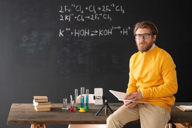 Insegnante di chimica barbuto fiducioso con libro aperto che si siede sul tavolo sulla lavagna e prepara lezione per studenti online