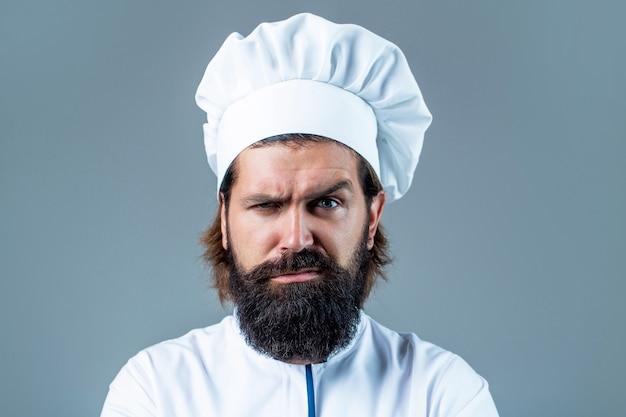 Chef maschio barbuto fiducioso in uniforme bianca. cuoco serio in uniforme bianca, cappello da cuoco. ritratto di un serio chef cuoco. chef barbuto, cuochi o fornaio. chef maschi barbuti isolati. cappello da cuoco.