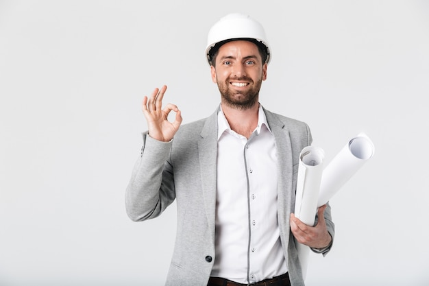 Fiducioso uomo barbuto builder che indossa tuta e elmetto protettivo in piedi isolato su un muro bianco, portando progetti, mostrando ok