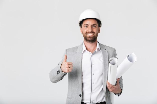 Costruttore di uomo barbuto sicuro che indossa tuta e elmetto protettivo in piedi isolato sul muro bianco, portando progetti, pollice in alto