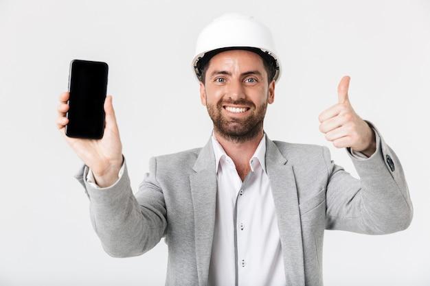 Costruttore di uomini barbuti fiduciosi che indossano tuta e elmetto protettivo in piedi isolato su un muro bianco, mostrando un telefono cellulare con schermo vuoto