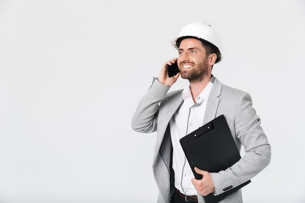 Costruttore di uomo barbuto sicuro che indossa tuta e elmetto protettivo in piedi isolato su un muro bianco, parlando al telefono cellulare