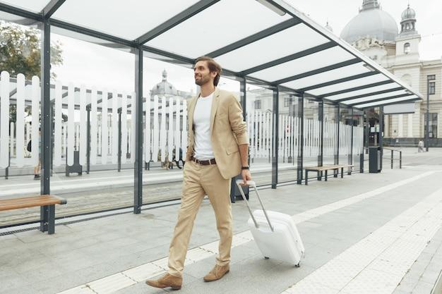 Fiducioso uomo barbuto vestito in tailleur elegante che cammina sulla strada con la valigia bianca