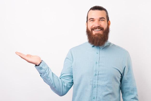 L'uomo barbuto sicuro che indossa la camicia ti sta presentando qualcosa.
