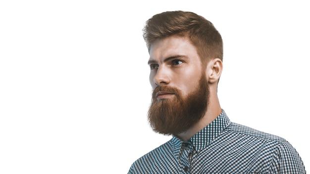 Fiducioso barbuto elegante uomo in attesa isolato su sfondo bianco. copia spazio a sinistra