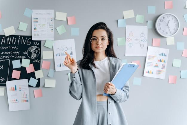 Bella ragazza sicura di affari con i documenti nelle mani sull'area di lavoro