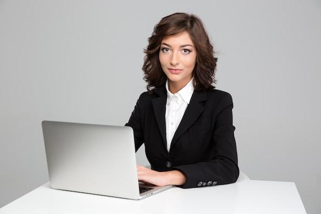 Bella giovane donna d'affari riccia sicura che si siede e lavora usando il laptop