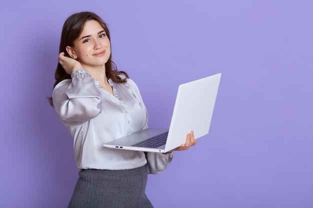 Impiegato femminile bello sicuro che indossa camicetta elegante in posa con il computer portatile in mano e guardando direttamente la fotocamera, manager che lavora, isolato sopra il muro lilla.