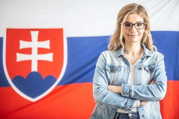 Fiduciosa bella ragazza slovacca con gli occhiali si trova di fronte alla bandiera del suo paese.