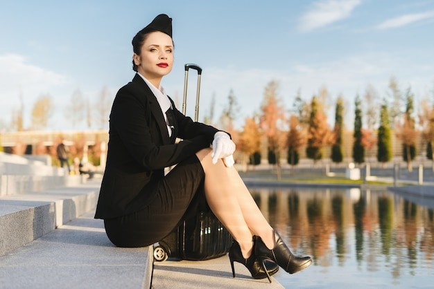 La bella hostess sicura della donna in uniforme si siede sui gradini, con la valigia