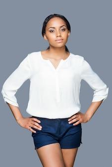 Bellezza sicura. attraente giovane donna africana che si tiene per mano sul fianco e guarda la telecamera mentre si trova in piedi su sfondo grigio