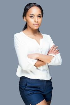 Bellezza sicura. attraente giovane donna africana che tiene le braccia incrociate e guarda la telecamera mentre è in piedi su uno sfondo grigio