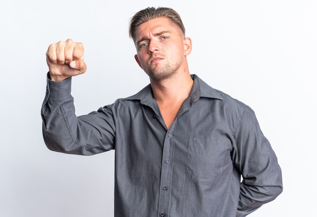 Fiducioso biondo bell'uomo che tiene il pugno alzato isolato sul muro bianco con copia spazio