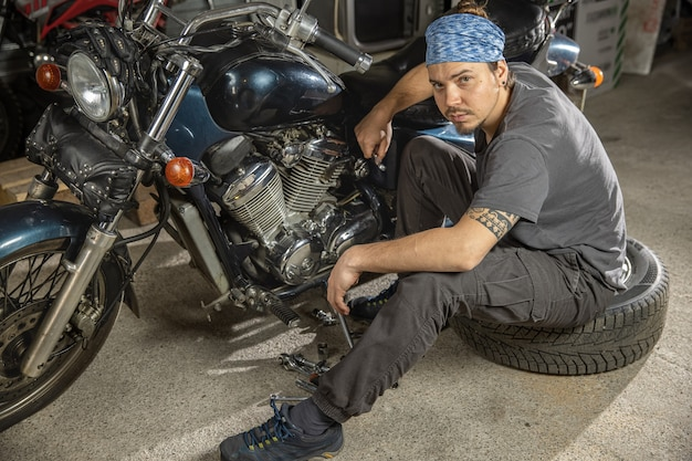 Fiducioso in bondana giovane in un negozio di riparazioni seduto di fronte a una moto retrò auto mech