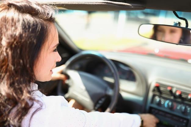 La donna castana sicura è seduta al volante di un'auto e l'autista donna sorridente guarda