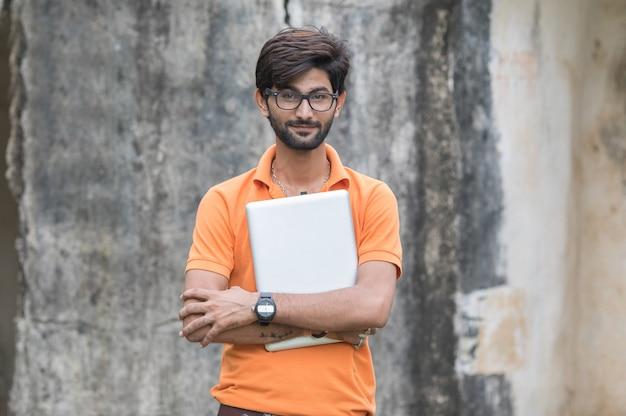 Esperto di affari fiducioso. fiducioso giovane uomo bello in maglietta e tenendo il computer portatile