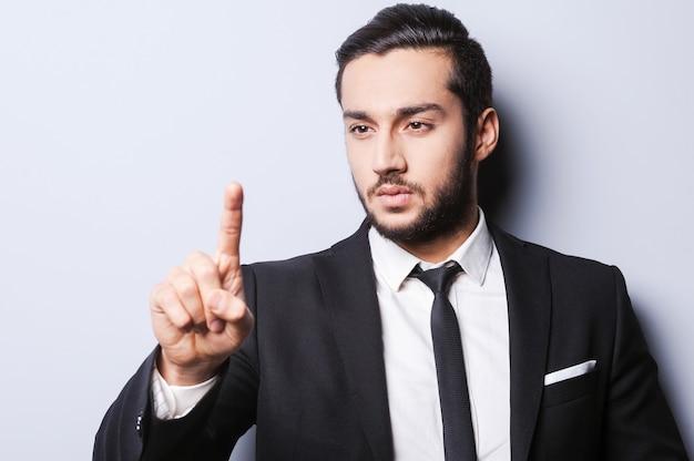 Esperto di affari sicuro. fiducioso giovane in abiti da cerimonia che punta e guarda il dito mentre si trova in piedi su uno sfondo grigio