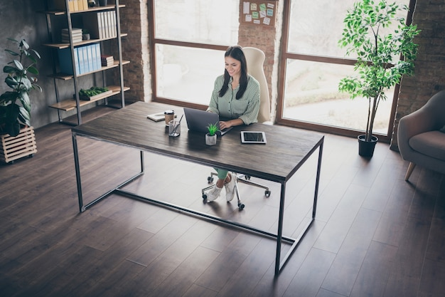 La signora fiduciosa di affari si siede la tabella usando il computer portatile all'ufficio moderno