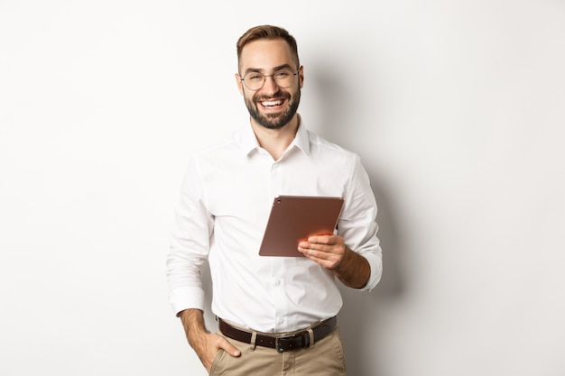 Fiducioso uomo d'affari in possesso di tavoletta digitale e sorridente, in piedi su sfondo bianco.