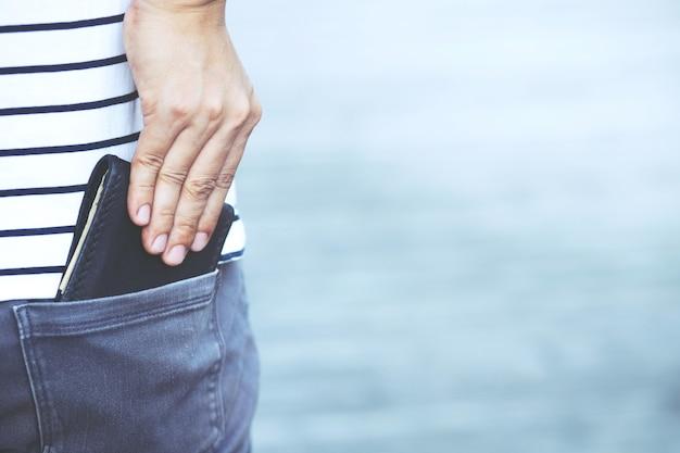 Uomo d'affari fiducioso in posa in sicurezza mantenendo il portafoglio nella tasca posteriore dei pantaloni della tasca posteriore. risparmio di denaro.