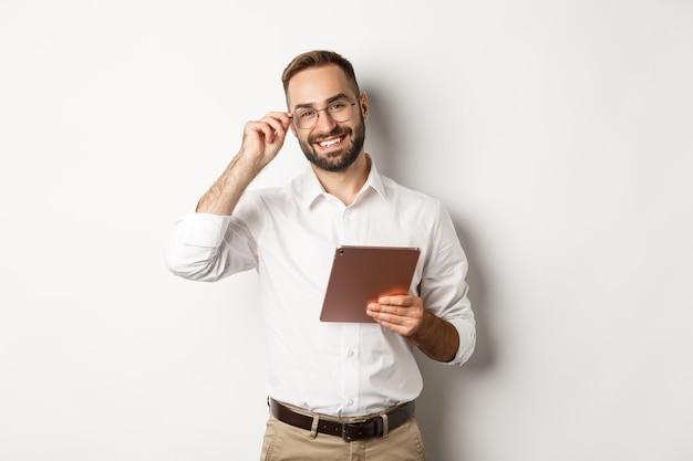 Fiducioso uomo d'affari lavorando su tavoletta digitale, sorridendo felice, in piedi su sfondo bianco.