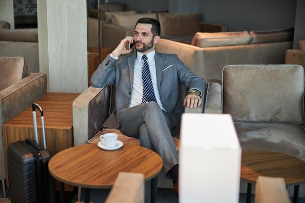 Responsabile aziendale sicuro che parla sullo smartphone