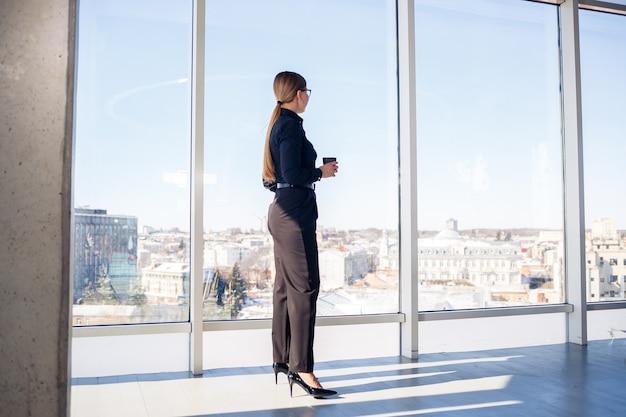 Capo donna d'affari fiducioso in piedi in un ufficio moderno o nella finestra dell'hotel godendo della vista della grande città, leader donna, imprenditore che pensa al successo futuro, pianificando nuove opportunità,