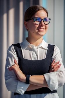 Capo donna d'affari fiducioso in piedi in un ufficio moderno con gli occhiali, leader femminile, imprenditore che pensa al successo futuro, pianificando nuove opportunità