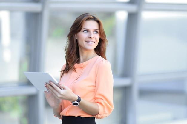 Fiduciosa donna d'affari con tavoletta digitale in ufficio offuscata