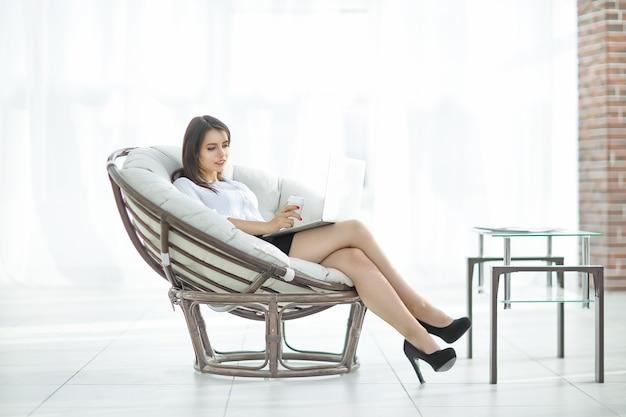 Donna d'affari sicura con documenti seduta intorno a una sedia comoda