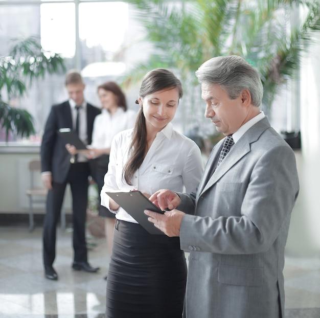 Fiducioso uomo d'affari e assistente discutendo documento di lavoro in piedi in un ufficio moderno