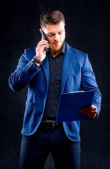 Uomo d'affari sicuro sta parlando al telefono con la cartella in mano isolata sul nero