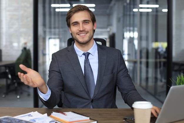 Uomo d'affari sicuro che guarda la telecamera parlando di strategia aziendale e piano aziendale, spiegando il successo aziendale.