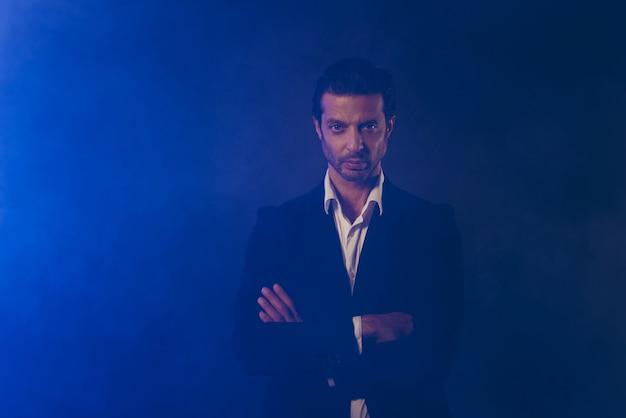 Fiducioso uomo d'affari in posa in camera oscura